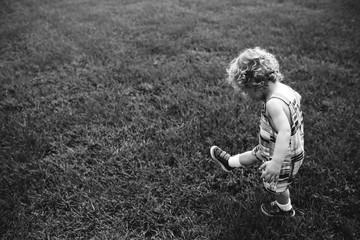 Boy with curls walking in grass