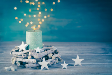 Christmas background with burning candle and bokeh lights