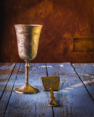 Photo of antique bocal for wine a old bronze spatula,  on the rough, scabrous wooden background.