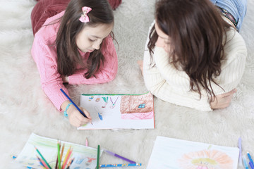 mom and daughter paint a picture lying on the floor