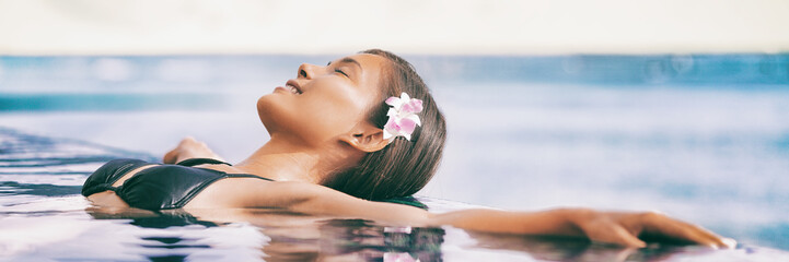 Wall Mural - Spa wellness resort infinity pool woman relaxing at hotel banner panoramic header. Relaxation travel vacation concept.