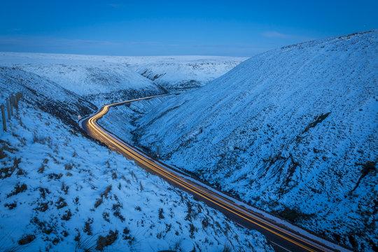Winter landscape and trail lights on Snake Pass, Peak District National Park, Derbyshire