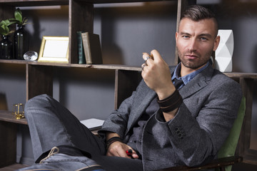 Expressive look of a handsome man in a business suit, who sits in a chair in a luxurious apartment with a smoking pipe.