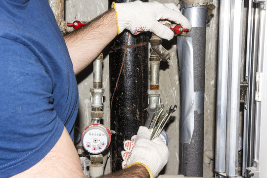 plumber repairs the pipes. A man from the service and maintenance of pipes and sewerage.