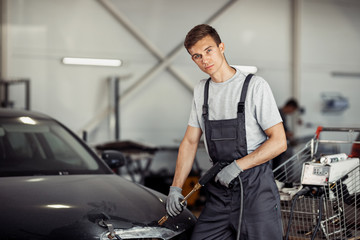 An attractive young mechanic in professinal unifors is at work at a car service