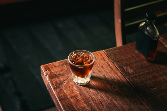 Cold brew coffee with ice cubes and the glass bottle on the wooden table from above. Urban coffee shop.