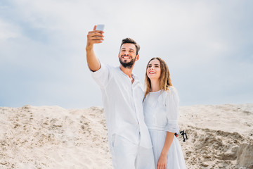 happy young couple in white clothes taking selfie in desert