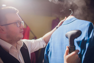 tailor cuts and sews a suit. A young man in the tailoring shop makes men's clothing. Custom-made clothing workshop. holds in her hand an electric iron. wet-heat treatment