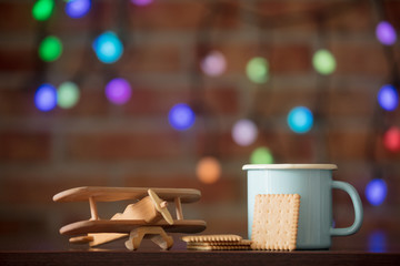 Hot cup of coffee, cookie and wooden plane with fairy lights on background. Christmas season