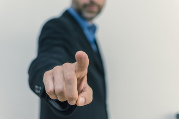 men in business suit pointing in front of camera