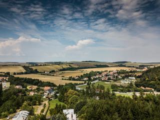 Drone flying above the trees and little town. Blue dramatic sky with green trees with little buildings.