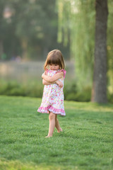 Miffed young girl walking barefoot through the fresh grass
