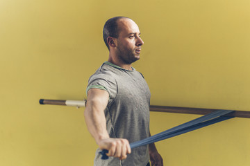 Confident young man exercising against yellow wall in gym