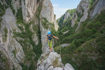 Female rock climber standing on top of craggy cliff