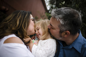 Close-up of parents kissing daughter at tourist resort