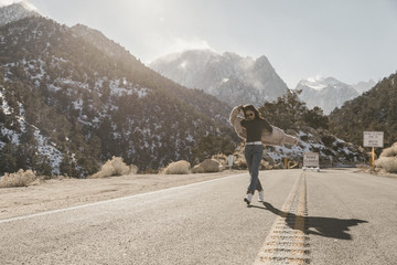 Full length of carefree young woman walking on road against mountains during sunny day