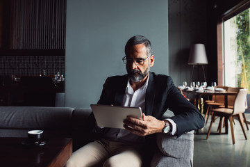 Businessman Reading on Tablet