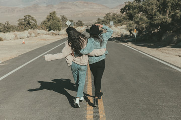 Rear view of happy female friends walking on road at desert during sunny day