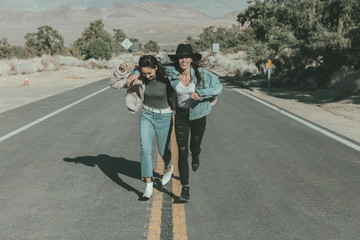 Full length of happy female friends running on road at desert during sunny day
