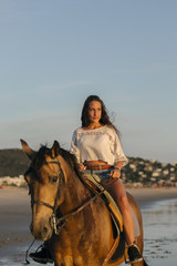 Teen riding horse at the beach