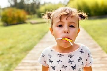 Portrait of a little girl eating lollipops
