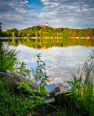 Chateau Konopiste at the sunset reflected in the water with rock foreground, Central Bohemia, Czech Republic.