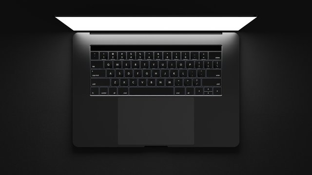 Top view of modern laptop isolated on dark background.