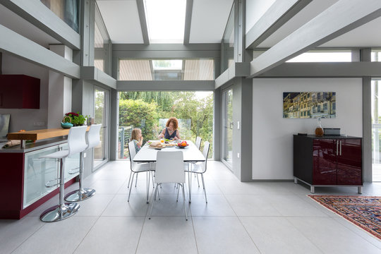 Mother and daughter eating lunch within a modern home.