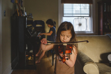 Siblings practicing musical instruments at home
