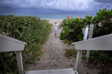 Rear view of girl walking amidst plants at beach