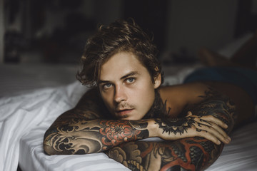 Portrait of shirtless tattooed man lying on bed at home