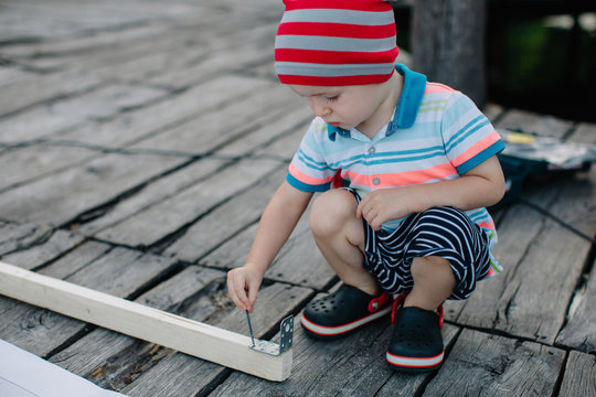 Little adorable boy playing with screws bolt