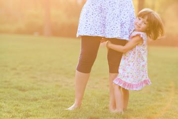 Portrait of sweet little girl hugging her mother's leg