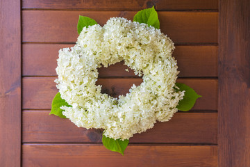 A wreath of white hydrangea on the wooden background