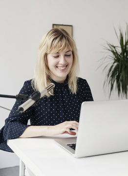 Young woman recording a podcast.