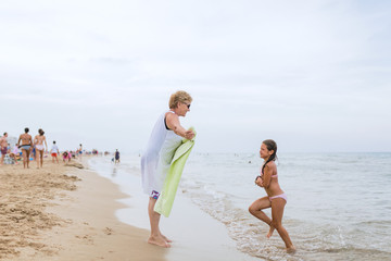Grandmother waiting her granddoughter with a towel in the seasho