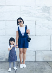 Toddler with auntie in matching overalls by marble wall