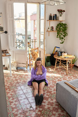 Girl in violet jacket and black boots sitting on floor with cros