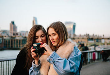 Cute twenties friends laughing and taking at photos  in front of the River Thames