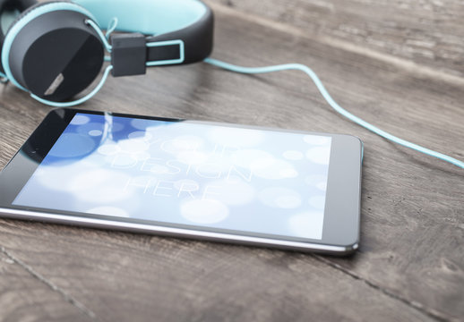 Tablet on Table with Headphones Mockup
