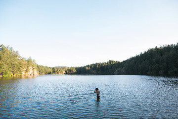 Mature woman preparing for early morning lake swim