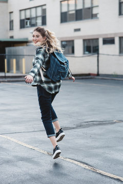 A young woman skipping outside of school