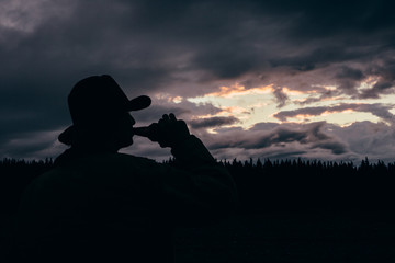 Silhouette of Man Drinking Beer at Magic Hour