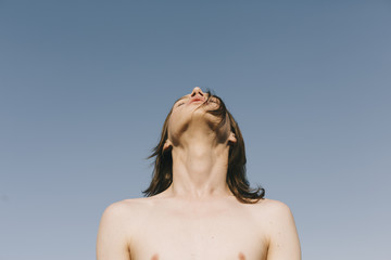 young androgyne on the blue sky background