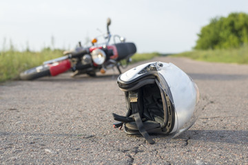 Photo of helmet and motorcycle on the road, the concept of road accidents