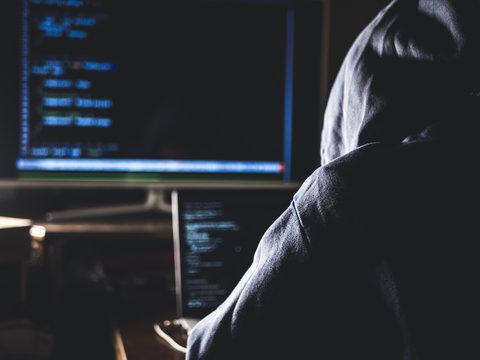hacker in hoodie typing code in program using laptop in dark studio