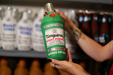British artist Lucy Sparrow, 32, holds a bottle of gin in her art installation supermarket in which everything is made of felt, in Los Angeles