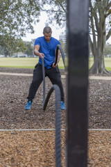 Fit latino doing outdoor rope exercises