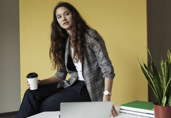 Confident young woman sitting on her desk.