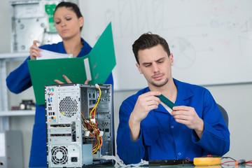 team of students examining and repairing computer parts